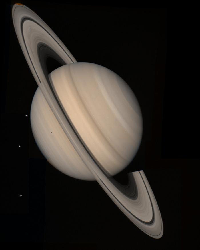 оваа слика која ги претставува вистинските бои на Сатурн е композитна фотографија направена од Војаџер 2 на 4 август 1981 година на оддалеченост од 21 км од траекторијата на леталото. Од лева страна се забележуваат трите ледени месечини на Сатурн.