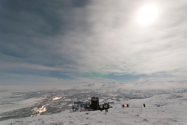 Полната Месечина ја рефлектира својата светлина од облаците и снегот и ја прави ноќта посветла од денот. Сликано над Aurora Sky Station. Во подножјето е Абиско, а помеѓу облаците и планините се провлекува северната светлина. Авторски права: Софија Спировска